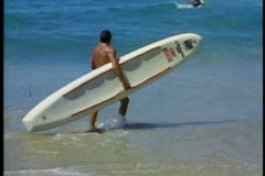Surfer holding surfboard, walking into ocean, Manly Beach, Sydney, Australia Stock Footage