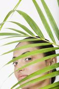 Indian woman behind palm frond Stock Photos
