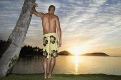 Stock Photo of Asian man watching sunset