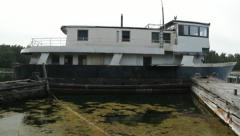Tilt up from algae in sea to derelict boat. Stock Footage