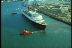 QE2 aerial, tugs pulling ship away from dock, wide shot Stock Footage