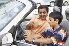 Middle Eastern father and son in new car Stock Photos