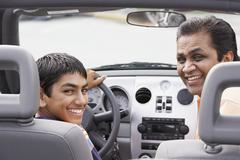 Middle Eastern father and son in new car - stock photo