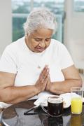 Senior African American woman saying grace Stock Photos