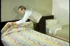 Steward, cabin on the QE2, turning down bed, placing Godiva Chocolates on bed Stock Footage