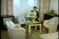 Man in QE2 cabin having breakfast reading Sydney Morning Herald, talent released Stock Footage