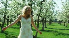 Woman dancing in a grove of flowering trees Stock Footage