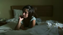 Woman laying on bed with deck of cards Stock Footage