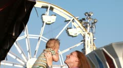 Woman with baby laughing at amusement park Stock Footage