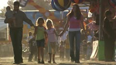 Family holding hands at amusement park - stock footage