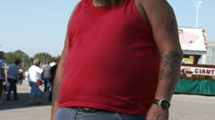 Mid section view of obese man with tattoos Stock Footage