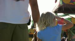 Family holding hands at amusement park Stock Footage