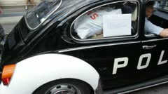 Vintage Volkswagen Beetle Police car takes part in Stockholm Gay Pride parade. Stock Footage