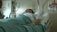 Stock Video Footage of Male doctor explaining to male patient in hospital bed