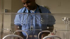 Male hospital worker caressing newborn in incubator Stock Footage