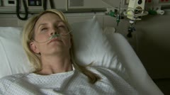 Woman in hospital bed with nasal cannula looking up Stock Footage