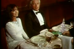 QE2 Princess Grill, couple in gown & tux, medium shot on banquette Stock Footage