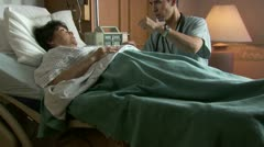 Male doctor explaining to mature woman in hospital bed Stock Footage