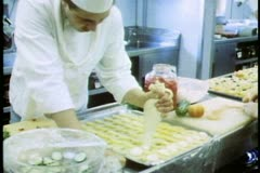 QE2, Queen Elizabeth 2, ship galley kitchen, medium shot, squeeze pastry bag - stock footage