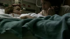 Woman caressing child in hospital bed Stock Footage