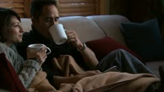 A couple drinking coffee on a couch Stock Footage