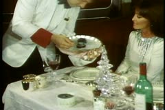 QE2 Princess Grill, couple in gown & tux, medium shot waiter spoons caviar - stock footage