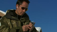 A man listening to an iPod putting on his gloves Stock Footage