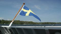 Swedish flag blowing in wind on stern of motor boat Stock Footage