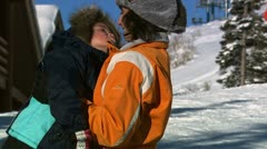 A mother and daughter embracing on a ski hill Stock Footage