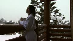 A woman on a snowy balcony drinking coffee Stock Footage