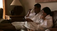 A couple enjoying a cup of coffee together watching television Stock Footage