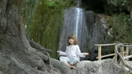 Little girl meditates in nature Stock Footage