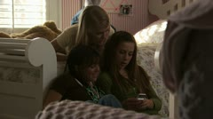 Three young girls sending a text message Stock Footage