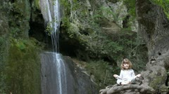 Little girl meditate by the waterfall Stock Footage