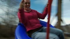 Woman on tire swing outdoors smiling Stock Footage