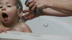 Mother washing baby's hair in bath - stock footage