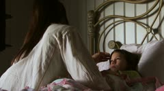 Girl in bed with mother stroking forehead Stock Footage