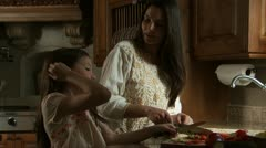 Mother and daughter cooking in kitchen - stock footage