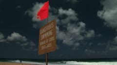 Wooden sign on beach with red wavy flag Stock Footage