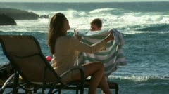 Mother drying son with beach towel outdoors Stock Footage