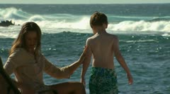 Mother applying sunscreen to son at beach Stock Footage