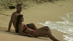 Couple reclining on sandy beach Stock Footage