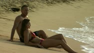 Stock Video Footage of Couple reclining on sandy beach