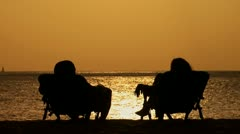 Couple in silhouette sitting in folding chairs on beach at dusk holding hands Stock Footage