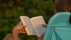 Rear view of woman reading outdoors Stock Footage