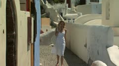 A woman walking in Santorini on her cellular phone Stock Footage