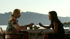 Two women dining outdoors at a scenic restaurant Stock Footage