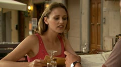 A woman outdoors at a restaurant looking at a menu Stock Footage