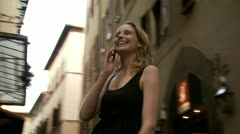 A woman walking while on her cellular phone - stock footage