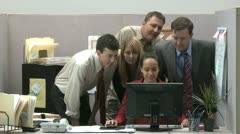 Office workers crowded around a computer watching and laughing Stock Footage